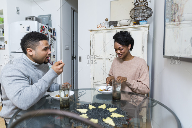 Couple sitting at glass table eating dinner