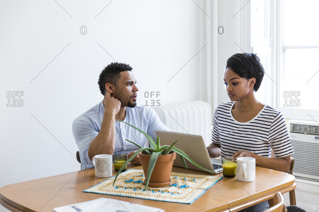 Couple sitting at wooden table using laptop
