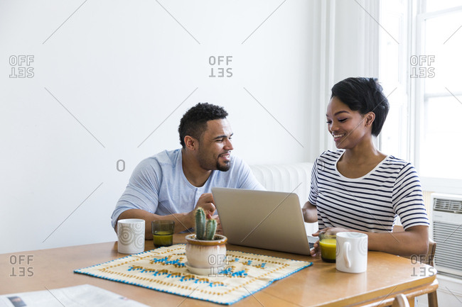 Happy couple sitting at wooden table using laptop