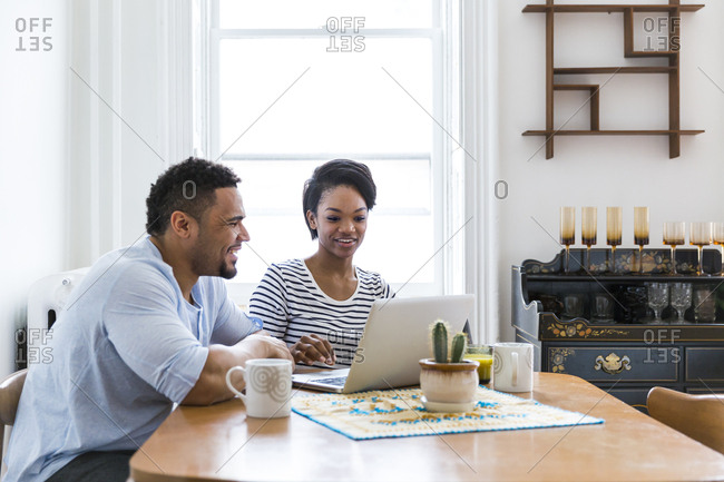 Happy couple at wooden table using laptop