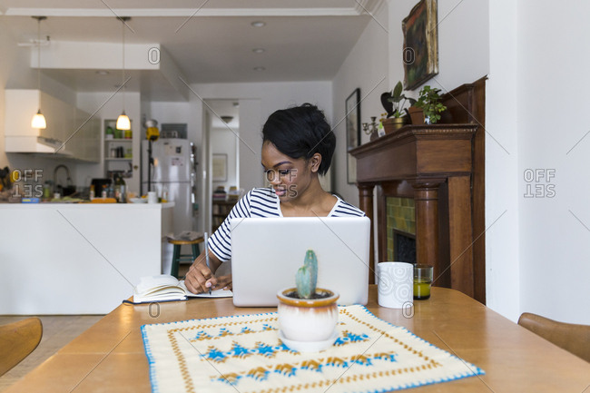 Woman writing notes in a book while using laptop