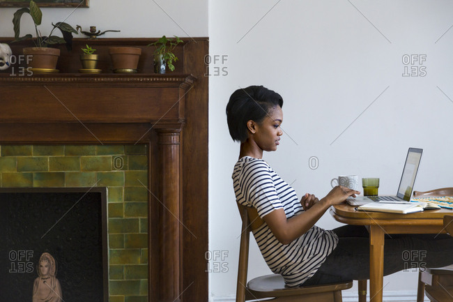Woman using laptop on dining room table