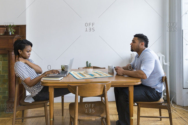 Couple sitting at wooden table using laptop and cell phone