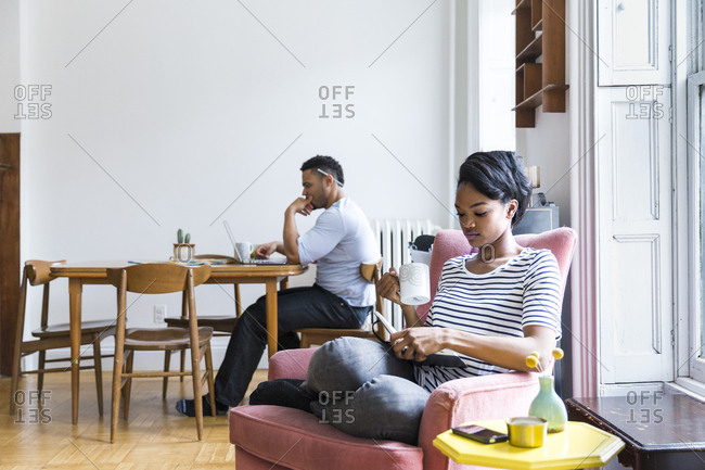 Woman reading book with man in background using laptop