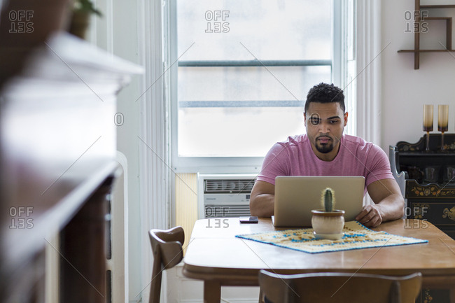 Man using laptop on dining room table