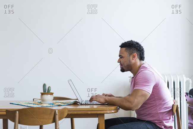 Man sitting at wooden table using laptop