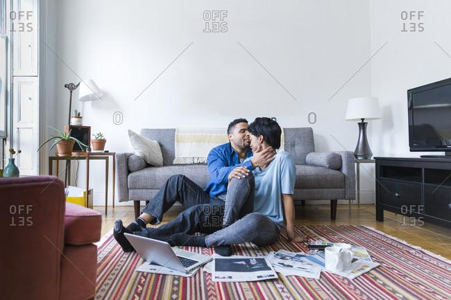 Couple sitting on living room floor kissing