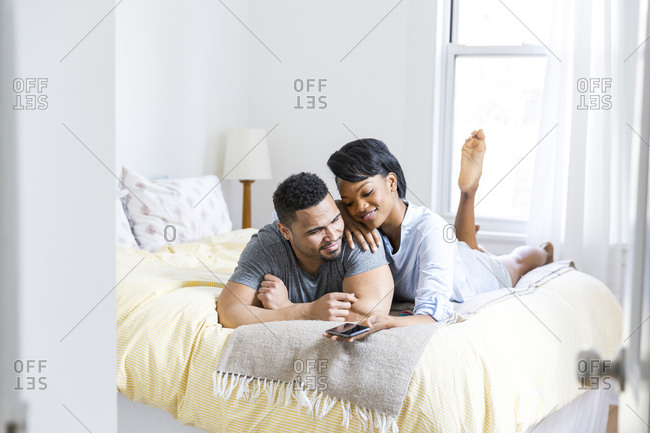 Couple on bed together holding cell phone