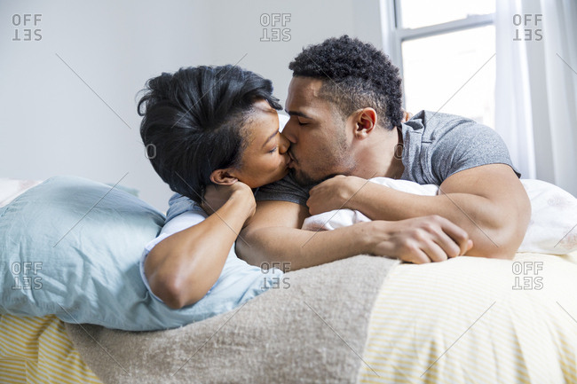 Couple kissing on a bed