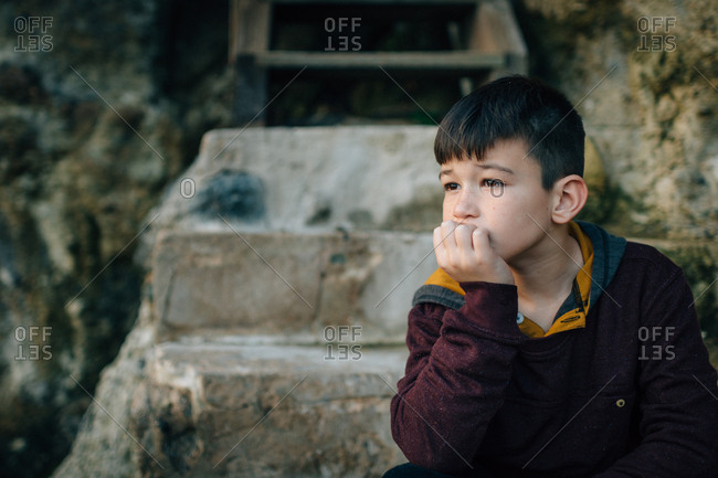 Contemplative boy sitting by wall