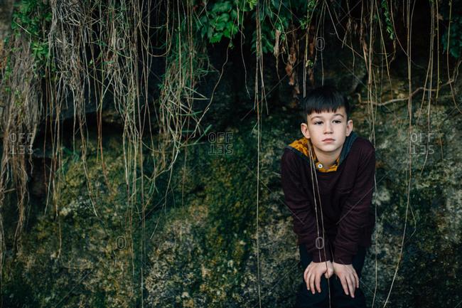 Boy underneath a rock overhang