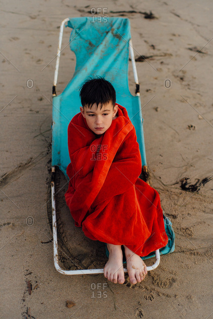 Boy wrapped in towel on a beach chair