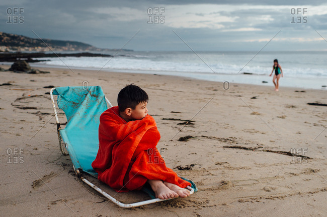 Boy wrapped in towel on beach chair