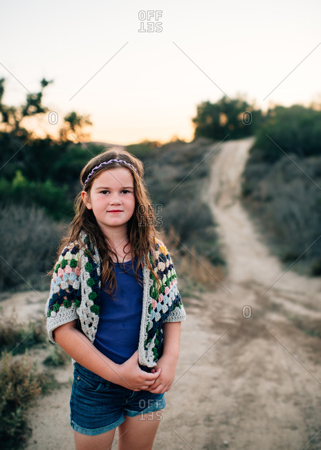 Girl in crocheted sweater on rural path