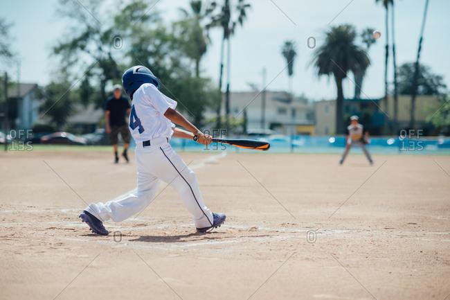 Boy swinging during baseball game