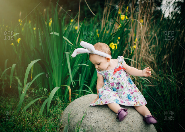 Girl in Easter outfit on a rock