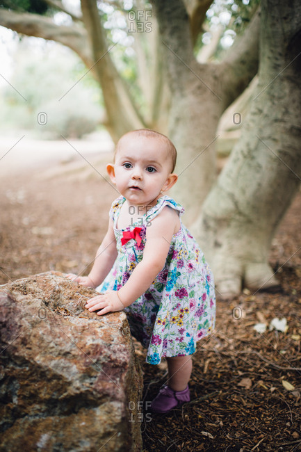 Toddler in dress leaning on rock