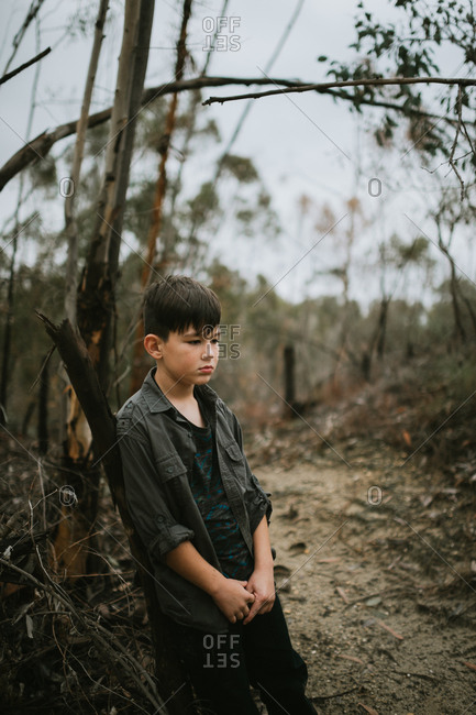 Boy leaning on tree alone in woods