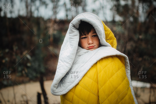 Boy in quilt in rural setting