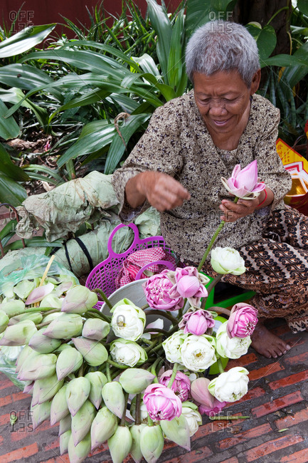 Phnom Penh, Phnom Penh, Cambodia - January 21, 2017: Woman selling lotus flowers in front of temple