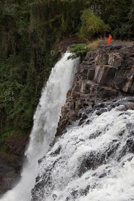 Sen Monorom, Mondulkiri, Cambodia - January 24, 2017: Buddhist monk standing on top of waterfall in the jungle