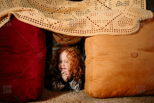 Child peeking out of pillow fort