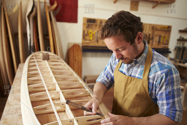 Man Building Bespoke Wooden Surfboard In Workshop