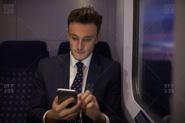 Businessman Sitting In Train Carriage Sending Text Message