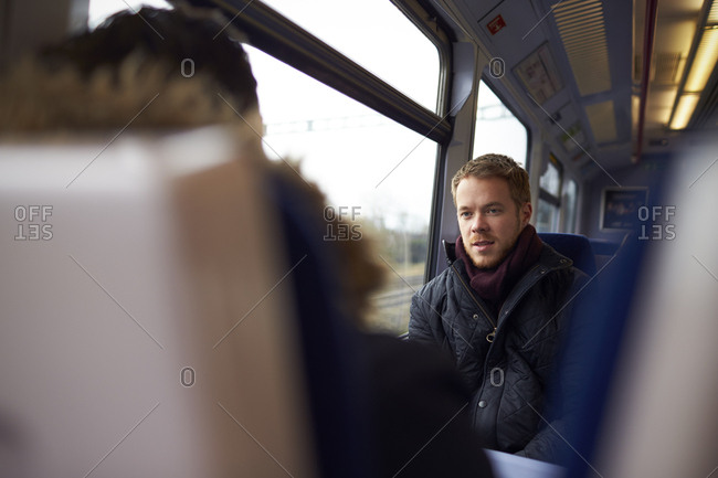 Two Men Sitting In Train Carriage And Talking