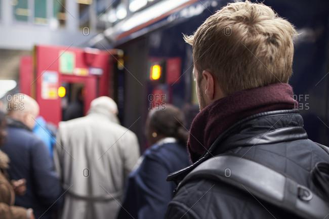 Man Boarding Train At Busy Railway Station