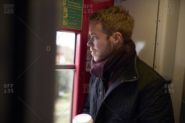 Young Man Standing In Train Carriage On Railway Journey