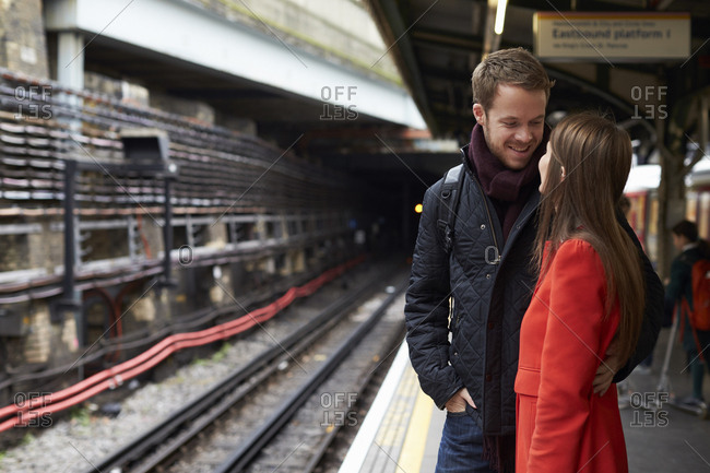 Young Couple Standing On Railway Station Platform Together