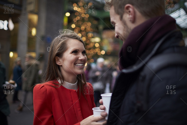 Young Couple Relaxing With Hot Drink At Christmas Market