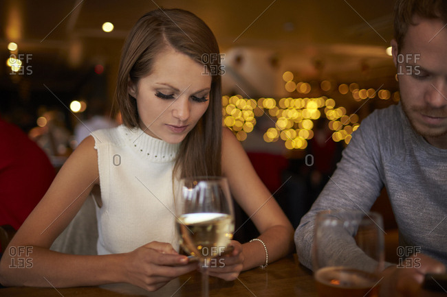 Young Couple Sitting In Bar Sending Text Message