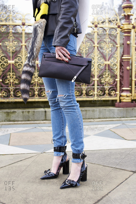 Woman in jeans and high heels holds clutch bag in the street