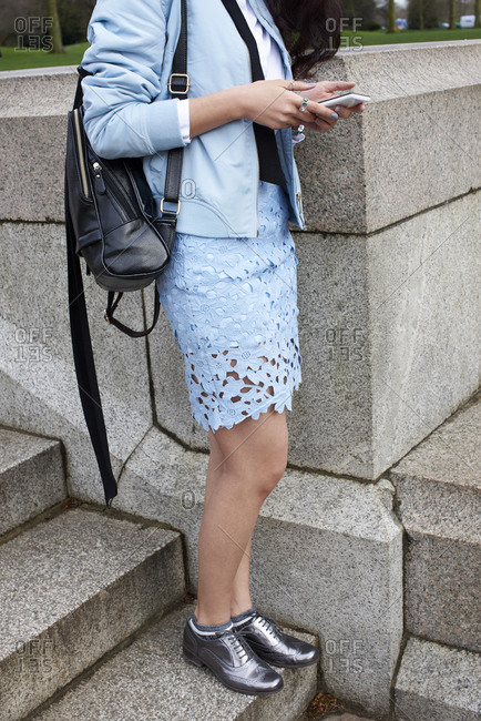 Woman in pale blue stands on step using smartphone, vertical