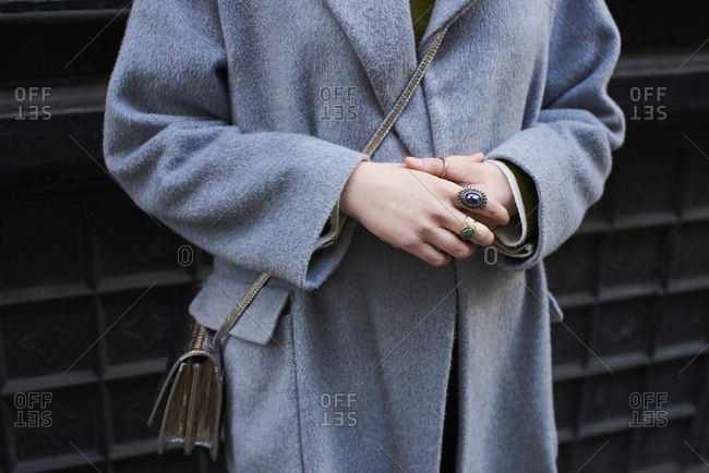 Midsection of woman wearing grey overcoat with hands clasped