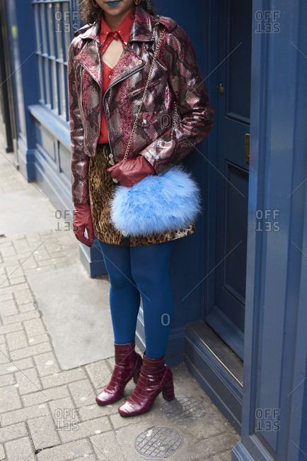 Woman in street with patent leather jacket and blue fur bag