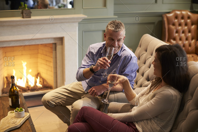 Mature Couple Sitting By Open Fire Drinking Champagne