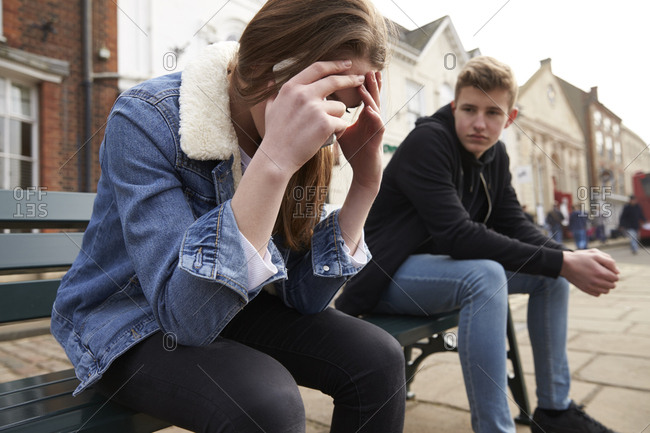 Teenager receiving sad news over phone while sitting on bench