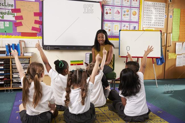 Teacher Asks Elementary School Pupils Question In Classroom