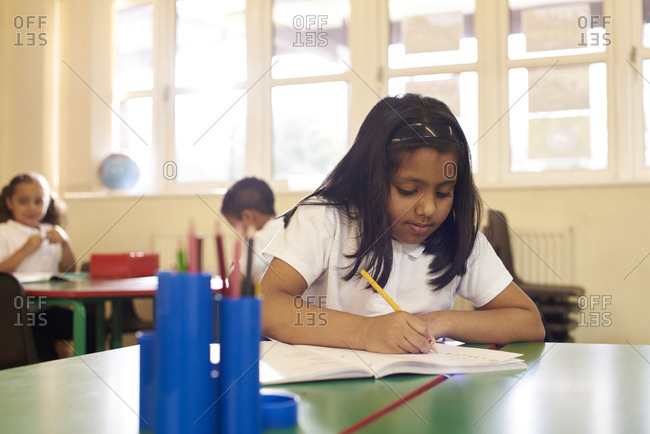 Female Pupil Working At Desk In Elementary School Classroom