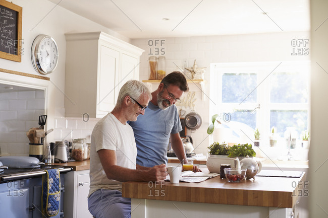 Male couple in their kitchen reading a paper in the morning