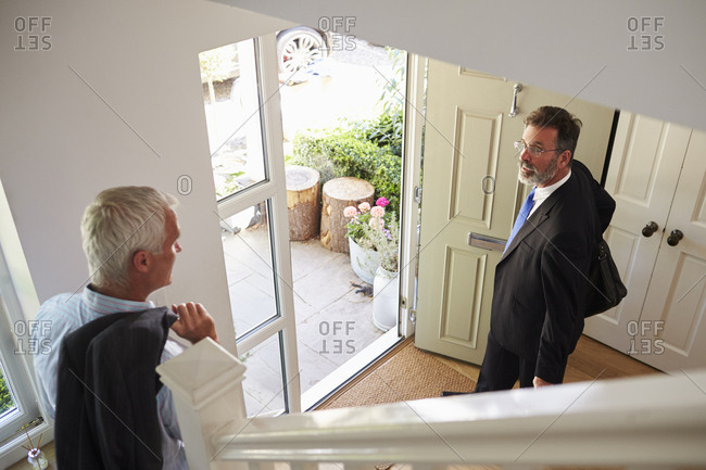 Male couple leave house for work, elevated view from stairs