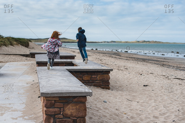Boy and girl running on a fence on a beach
