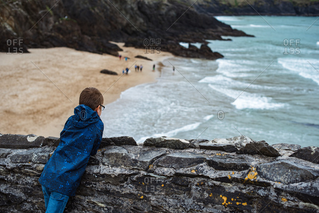 Boy looking at beach and cliffs in Ireland