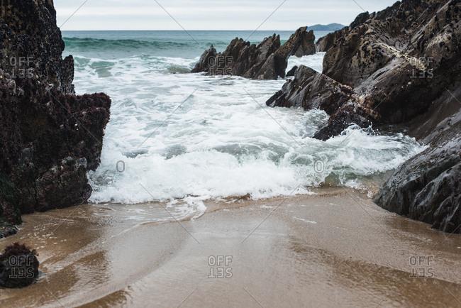 Sea waves coming through rocks on a beach