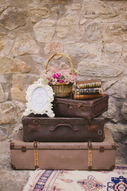 Obidos, Portugal - February 4, 2017: Books, bouquet and picture frame on a stack of vintage suitcases