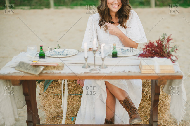 Portugal - February 4, 2017: Bride at a rustic table in a white dress and work boots smiling
