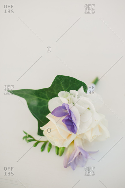 Boutonniere of white roses and purple flowers